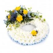 SYM-319 White Massed Wreath with Blue & Yellow Spray