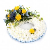 SYM-319 White Massed Wreath with Blue & Yellow Spray